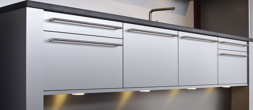 This creative quality kitchen has a sink bridge construction with ground clearance. The made-to-measure stainless steel bar handles for the aluminium fronts can only be provided by a real kitchen specialist.